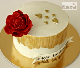 homemade anniversary cake with gold heart and red rose design