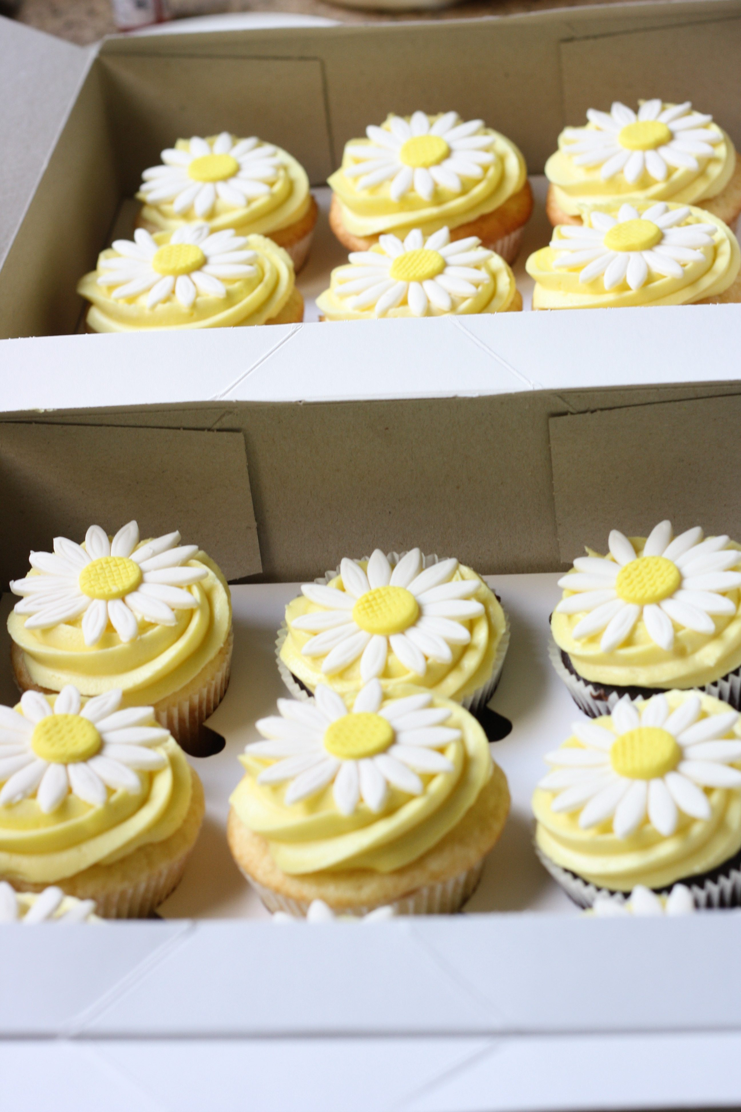 homemade cupcakes with yellow icing and flower topper