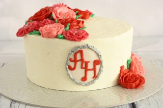 round white cake topped with pink and red roses anniversary cake